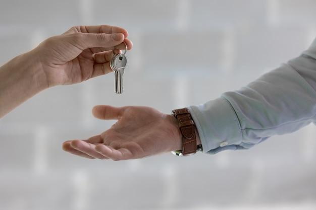 Die schlüssel zu einer neuen wohnung oder einem haus halten eine frau oder ein mann mit einem oder mehreren schlüsselbunden