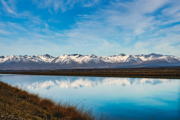 Die schneebedeckte bergkette der südalpen in der nähe von twizel spiegelte sich im stillen wasser des kanals wider, der unter einer wackeligen wolke aus dem rautaniwha-see fließt