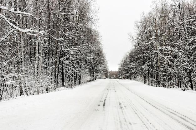 Die schneebedeckte winterstraße führt durch den wald