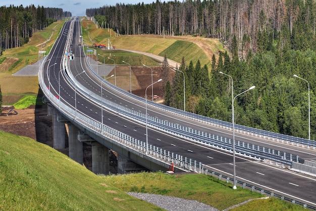 Die schnellstraße durchquert den wald, die stahlbockbrücke wird von stahlbetonstützen getragen.