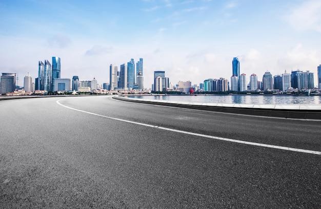 Die schnellstraße und die moderne skyline der stadt befinden sich in qingdao, china.