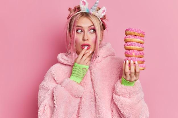 Die schockierte, gut aussehende frau starrt auf einen haufen donuts und merkt, wie viel kalorien sie essen wird