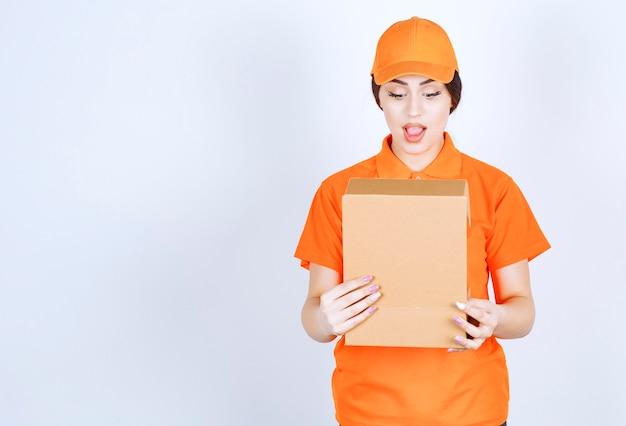Die schockierte lieferfrau, die in das paket schaut
