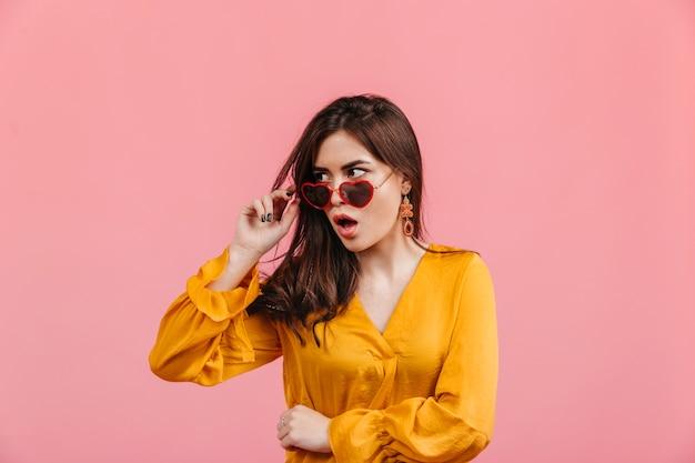 Die schockierte, stilvolle dame nimmt ihre herzförmige brille ab. schuss des brünetten mädchens in der hellen bluse auf der isolierten rosa wand.
