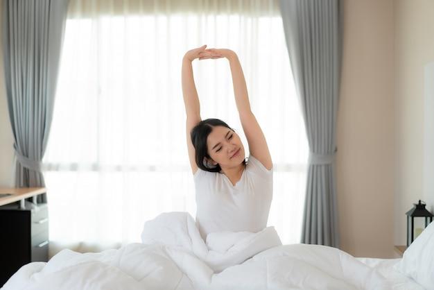 Die schöne asiatin, die hände und körper im bett nach ausdehnt, wachen im schlafzimmer zu hause auf. konzept für den start neuer tag mit glück. copyspace auf der linken seite. junges glückliches arbeitendes weibliches leben