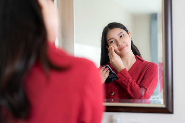 Die schöne asiatin, die rot trägt, kleidete den puderquast setzen, der zu hause in spiegel in ihrem schlafzimmer schaut. make-up am morgen immer bereit, bevor sie zur arbeit gehen.