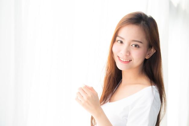 Die schöne asiatische frau, die das fenster und das lächeln steht, wachen auf.