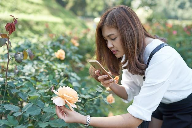 Die schöne asiatische frau, die foto für nimmt, stieg