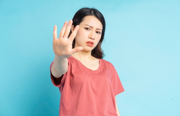 Die schöne asiatische frau hielt ihre hand vor sich und bat darum, nicht näher zu kommen