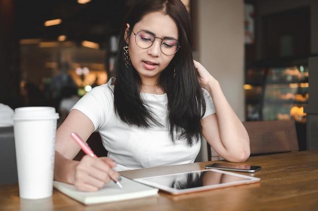 Die schöne asiatische geschäftsfrau, die gläser trägt, arbeitet und schreibt auf notizbuch im café.