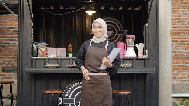 Die schöne asiatische kellnerin bringt eine liste mit gebrauchsfertigen menüs am café-standcontainer