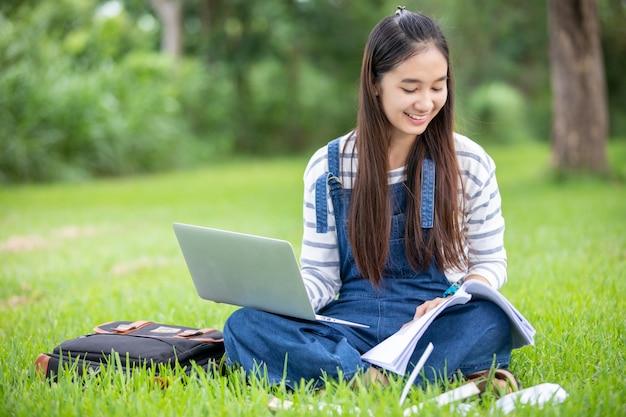 Die schöne asiatische studentin, die bücher hält und auf park im sommer für lächelt und lernt und bildet, entspannen sich zeit