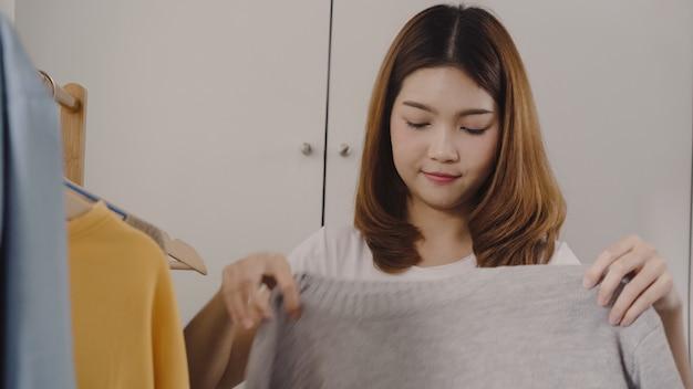 Die schöne attraktive junge asiatin, die zu hause ihre modeausstattung wählt, kleidet im wandschrank