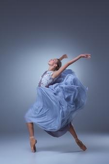 Die schöne ballerina, die im langen blauen kleid auf blauem hintergrund tanzt