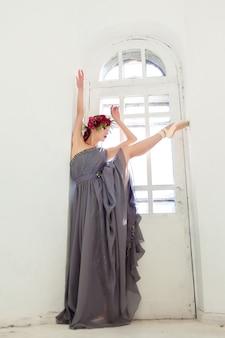 Die schöne ballerina posiert im langen grauen kleid