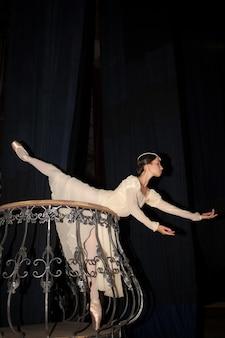 Die schöne ballerina posiert im langen weißen kleid
