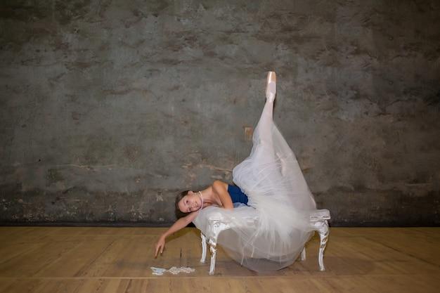 Die schöne ballerina posiert im langen weißen rock