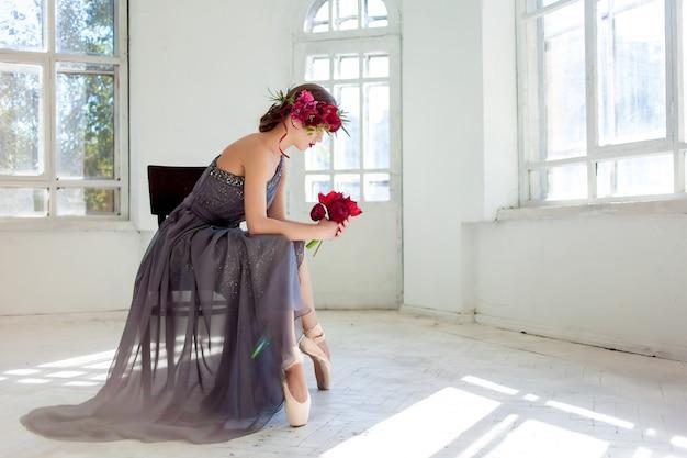 Die schöne ballerina sitzt in einem langen grauen kleid