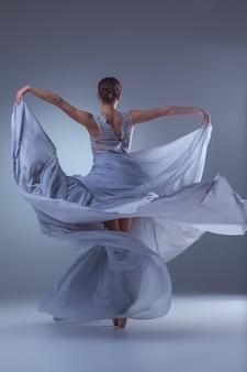 Die schöne ballerina tanzt im langen lila kleid auf lila hintergrund