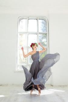 Die schöne ballerina tanzt in langem grauem kleid