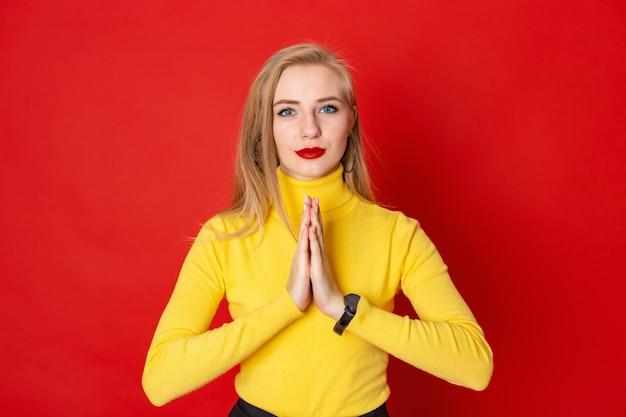 Die schöne blonde frau, die auf rotem hintergrund mit grußgesten namaste steht.