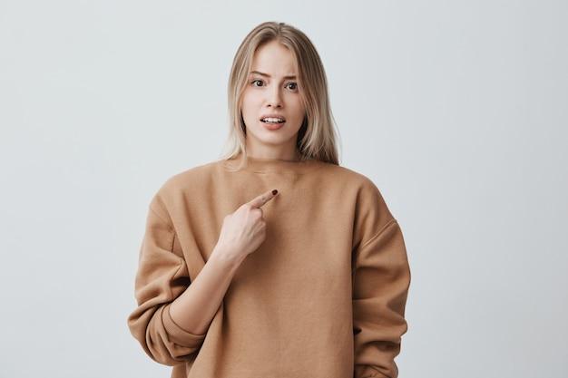 Die schöne blonde frau wird beschuldigt, etwas getan zu haben, das sie nicht gemacht hat. sie zeigt mit dem zeigefinger auf sich selbst, runzelt die stirn, ist unzufrieden und wütend. gesichtsausdruck und negative emotionen