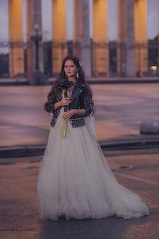 Die schöne braut in einem hochzeitskleid und einer lederjacke mit einem blumenstrauß. hochzeitskonzept. abendfotografie