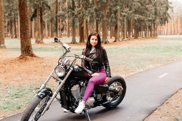 Die schöne brünette fährt motorrad im park