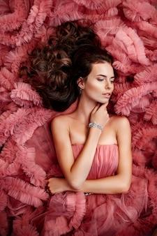 Die schöne brunettefrau mit dem gelockten haar, zartes make-up, das in einem hochzeitskleid aufwirft.