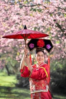 Die schöne chinesische junge frau, die rotes traditionelles cheongsam im kirschblütengarten trägt