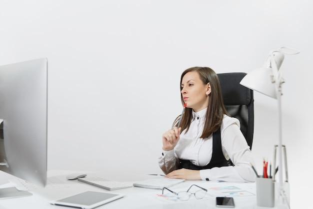 Die schöne ernsthafte und versunkene braunhaarige geschäftsfrau in anzug und brille sitzt am schreibtisch und arbeitet am computer mit modernem monitor mit dokumenten im hellen büro,