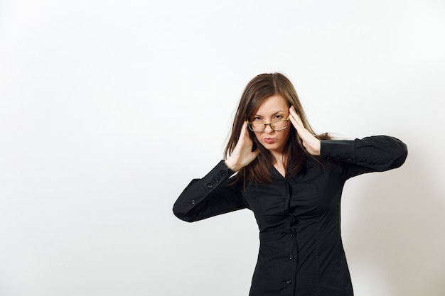 Die schöne europäische junge sexy braunhaarige frau mit brille für den anblick mit gesunder, sauberer haut und charmantem lächeln, gekleidet in einem dunklen schwarzen hemd, das auf weißem hintergrund genießt. emotionen-konzept.