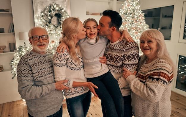 Die schöne familie steht neben dem weihnachtsbaum