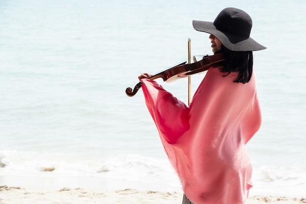Die schöne frau, die violine auf dem strand spielt
