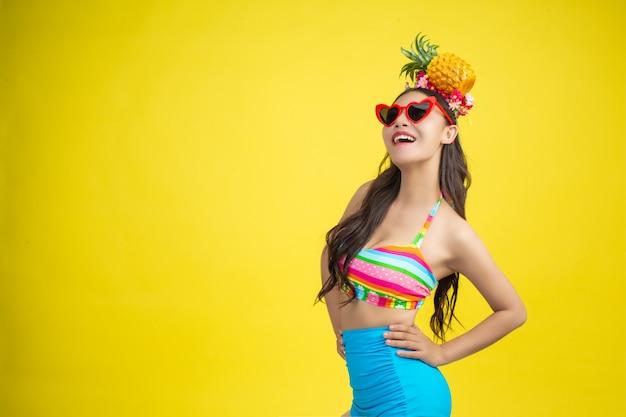 Die schöne frau in einem badeanzug, der eine ananas hält, wirft auf gelb auf