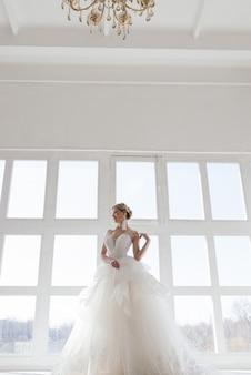 Die schöne frau posiert in einem hochzeitskleid im luxus-interieur