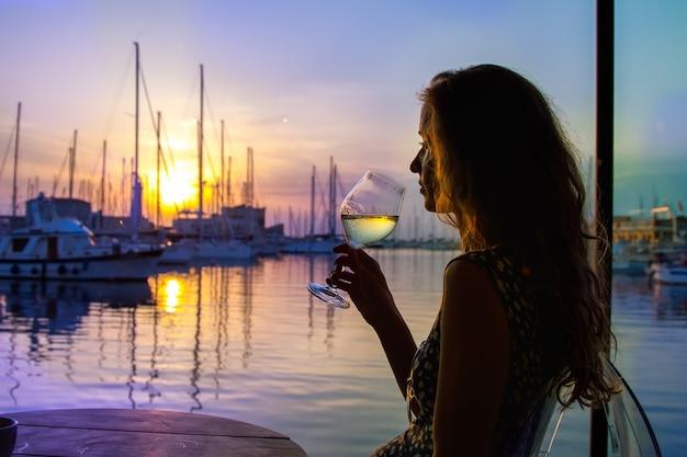 Die schöne frau trinkt wein und beobachtet den untergang der sonne