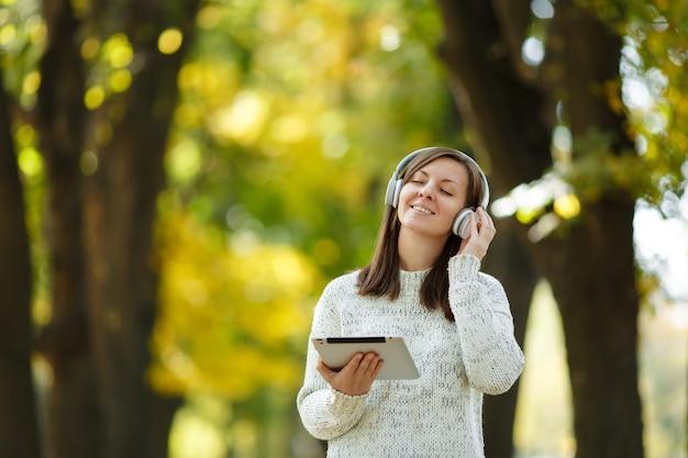 Die schöne fröhliche, fröhliche braunhaarige frau im weißen pullover mit einem tablet, das an einem warmen tag musik in den weißen kopfhörern im herbstpark hört. herbst in der stadt.