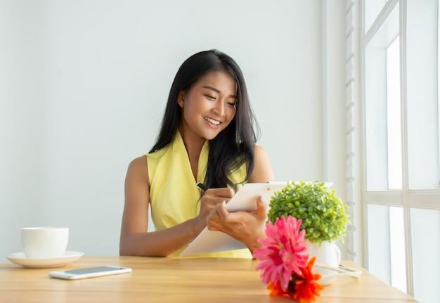 Die schöne geschäftsfrau, die ein gelbes hemd trägt, sitzt im büro und prüft dokumente, um seine geschäftspläne glücklich zu überprüfen