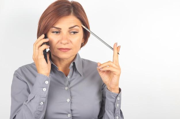 Die schöne geschäftsfrau spricht am telefon mit einem bleistift in ihrer hand