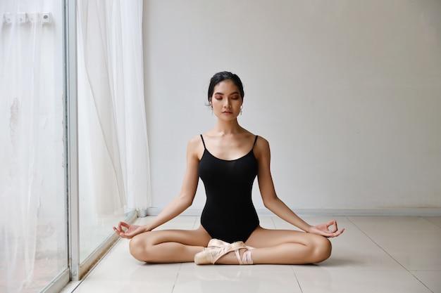 Die schöne gesunde asiatische frau im ballettkleid herein genießend meditiert mit yogahaltung zu hause mit entspannung
