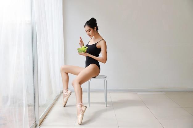 Die schöne gesunde und sportliche asiatische junge frau, die salatschüssel hält und essen nach der ausbildung