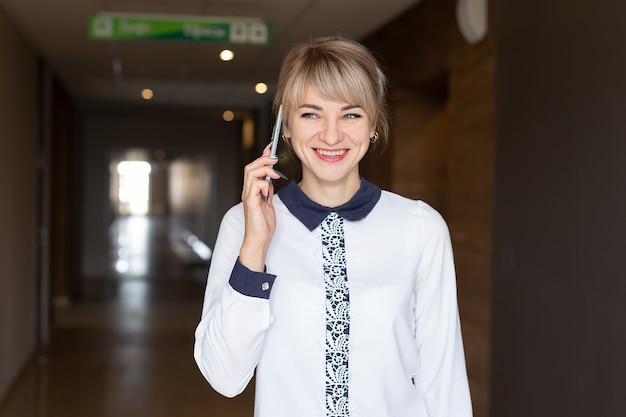 Die schöne glückliche blondine spricht am telefon