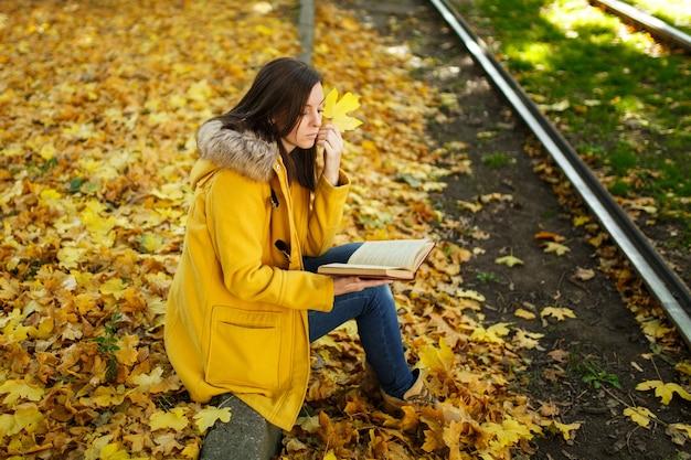 Die schöne glückliche braunhaarige frau in gelbem mantel und jeans sitzt allein im park in der nähe der straßenbahnschienen und liest an einem warmen herbsttag ein buch. herbstgelbe blätter.