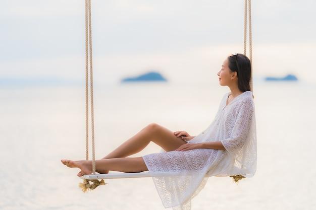 Die schöne junge asiatische frau des porträts, die auf dem schwingen um strandseeozean für sitzt, entspannen sich