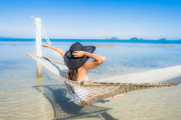 Die schöne junge asiatische frau des porträts, die auf hängematte um seestrandozean für sitzt, entspannen sich