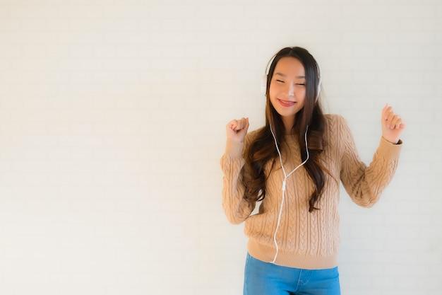 Die schöne junge asiatische frau des porträts, die glücklich ist, genießen mit, musik zu hören