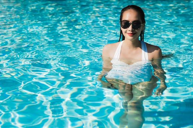 Die schöne junge asiatische frau, die glücklich ist und lächeln im swimmingpool für entspannen sich reise und ferien