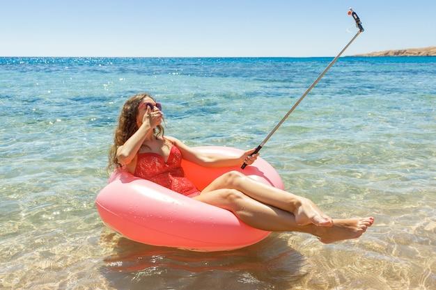 Die schöne junge entspannende frau und macht selfie auf aufblasbarem donut im meer