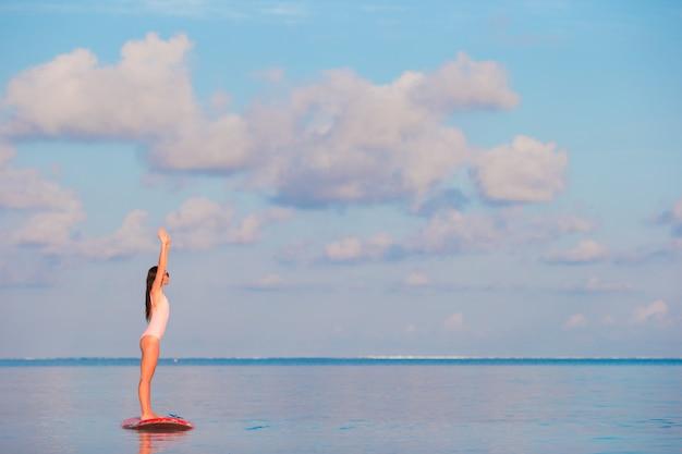 Die schöne junge frau, die an surft, stehen oben radschaufel an den exotischen ferien